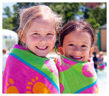 Children wrapped in towels smiling at waterpark